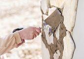 stock photo of mason  - Mason putting decorative natural stones on a wall  - JPG