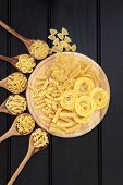 picture of olive shaped  - Pasta selection on a wooden board and in olive wood spoons over dark wood background - JPG