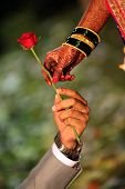 picture of mehendi  - A groom offering a red rose to his bride whose hand is beautifully decorated with traditional bangles and mehendi - JPG