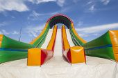 image of inflatable slide  - Striking canvas colors closeup of playground inflatable air slide apparatus - JPG