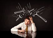 picture of beats  - Young depressed businessman sitting under white drawn beating hammer marks - JPG