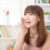 stock photo of shout  - Portrait of happy Asian girl shouting and smiling at home - JPG