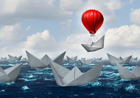 foto of boat  - Business advantage concept and game changer symbol as an ocean with a crowd of paper boats and one boat rises above the rest with the help of a red hot air balloon as a success and innovation metaphor for new thinking - JPG