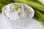 Bowl of tzatziki, with celery behind.  Delicious Greek yoghurt dip.