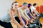 foto of exercise bike  - Happy people in a row exercising with bicycles in a gym - JPG