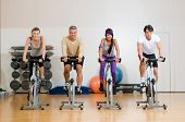 stock photo of gym workout  - Happy active people exercising with bicycles in a gym - JPG