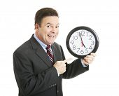 Businessman eagerly pointing to a clock that reads almost 5:00 pm.  He's ready to go home.  Isolated