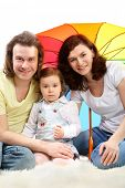 Happy young family - mother, father and little daughter - are sitting under colored umbrella on a white fluffy fur poster