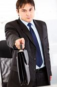 Authoritative business man standing at office desk and giving briefcase. Close-up.