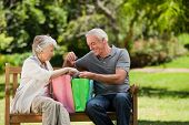 stock photo of old couple  - Retired couple with shopping bags - JPG