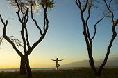 image of pranayama  - silhouette of woman practicing yoga at sunset on the Island of Maui in Hawaii - JPG