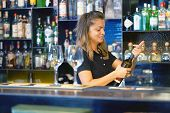A Bartender Woman Smiles And Opens A Bottle Of White Wine For The Client Of The Hotel Bar. Shelves W poster