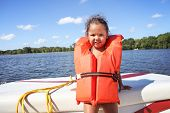 Preschool age girl wearing a life jacket and standing in a boat  poster