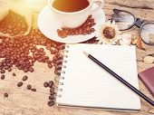 Hot Coffee Cup With Coffee Bean And Notebook With Pencil On Wooden Table. Coffee Background Menu For poster
