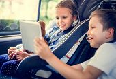 Sister and brother playing with digital devices in the car poster