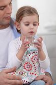 Father giving his daughter a glass of water to drink