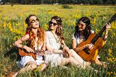 Three Cute Hippie Girl Lying On The Plaid Outdoors, Best Friends Having Fun And Laughing, Play Ukule poster