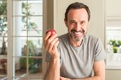 Middle age man eating healthy red apple with a happy face standing and smiling with a confident smil poster
