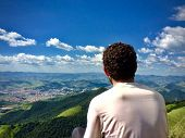Young Man Sitting And Looking Deep To The Horizon In A Mountain poster