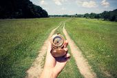 Man with compass in hand on rural road. Travel concept poster