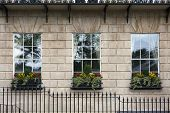 Georgian window triptych. Detail of windows with windowboxes and wrought iron railings on facade of