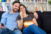 Young Couple Watching Tv At Home And Having Fun poster