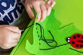 Child Making Felt Soft Toy Of Green Leaf And Red Ladybag . Child Diy Activity. Close-up. Children Ha poster