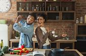 Black Couple Dancing Near Table With Food In Kitchen. Family Having Fun While Cooking poster