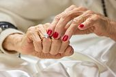 Old Woman Touching The Diamond On Her Finger. Senior Woman Hands With Beautiful Red Manicure Wearing poster