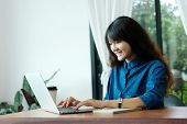 Young Asian Woman In Casual Style Using Laptop Computer In Room Background, People And Technology, W poster