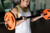 Determined young man holding a barbell with supinated grip while exercising bicep curls from standin poster