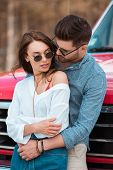 Tender Beautiful Couple In Sunglasses Hugging Near Red Car poster