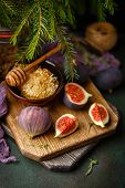 Juicy Fresh Whole Fig Fruits And One Cut Figs And Bowl Of Honey In Honeycombs On Wooden Cutting Boar poster