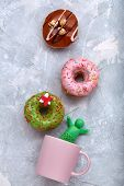 Colored Donuts On A Gray Background With A Coffee Mug. Top View, Donuts Spread Out Over A Mug Imitat poster