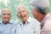 stock photo of bench  - Active retirement group of three old male friends talking and laughing on bench in public park - JPG