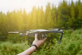 A Man Catching Drone With His Hand.photographer Controls A Quadcopter Drone To Take Aerial View Phot poster