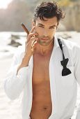 Great looking sexy male model with open white shirt and loose bow tie smoking cigar on beach