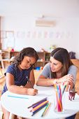 Beautiful teacher and toddler girl drawing draw using colored pencils at kindergarten poster