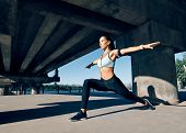 Young Sporty Woman Doing Yoga Asana Warrior I Pose Outdoors Under Industrial Bridge. Practicing Yoga poster