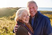 Portrait Of Loving Active Senior Couple Walking Along Coastal Path In Autumn Together poster