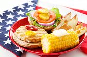 Healthy turkey burger on whole grain bun, with baked potato wedges and corn on the cob. Low fat picn