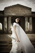 stock photo of supernatural  - Pretty gothic girl posing with sword on an old cemetery - JPG