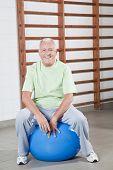 Feliz, sênior homem senta-se sobre uma fitball.