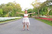 Portrait Of Happy Little Girl Closed Eyes And Open Wide Her Arms Standing On Road In The Garden. poster