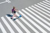 Girl Carrying Scooter And Crossing Road On Way To School. Zebra Traffic Walk Way In The City. Pedest poster