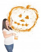 A pretty preteen flinging orange paint to create a splattered Halloween pumpkin.  On a white background with plenty of space below the pumpkin for your text.