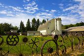 stock photo of dairy barn  - An old dairy farm with fence made from old wheels in the Palouse - JPG