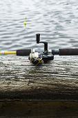 Fishing Reel On Log In Lake