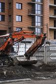 Orange Excavator Works On Construction Site With A Gravel And Carry It Fromone Place To Another. Hea poster