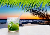Cocktail Mojito in Balearic island sunset and palm trees [ photo-illustration]